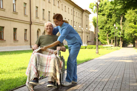 Happy nurse assisting elderly man in wheelchair at park