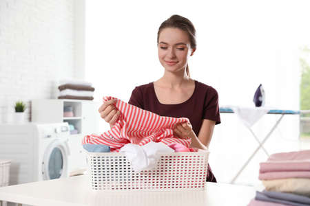 Happy woman with clean laundry at table indoors Standard-Bild - 129176323