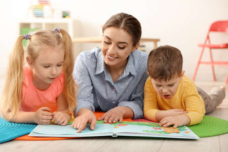 Kindergarten teacher reading book to children indoors. Learning and playing