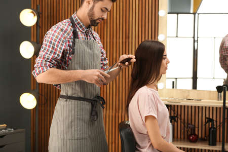 Barber making stylish haircut with professional scissors in beauty salon Stok Fotoğraf