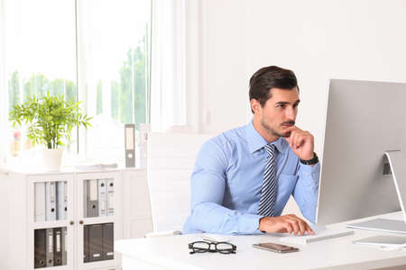 Handsome young man working with computer at table in office Zdjęcie Seryjne