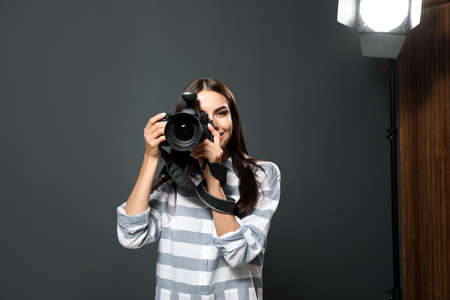 Professional photographer taking picture in modern studio