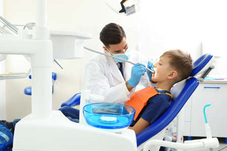 Professional dentist working with little boy in clinic Stok Fotoğraf