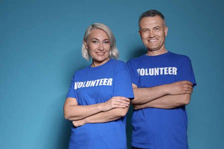 Portrait of volunteers in uniform on blue background 스톡 콘텐츠