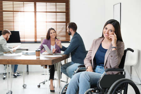 Young woman in wheelchair with colleagues at office