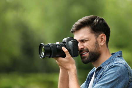 Photographer taking photo with professional camera in park Stock fotó