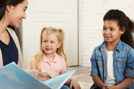 Kindergarten teacher reading book to cute little children indoors Zdjęcie Seryjne
