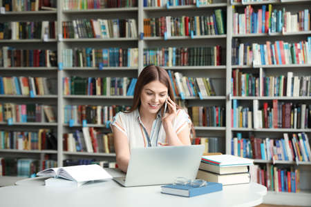 Young woman talking on phone and working with laptop at table in library