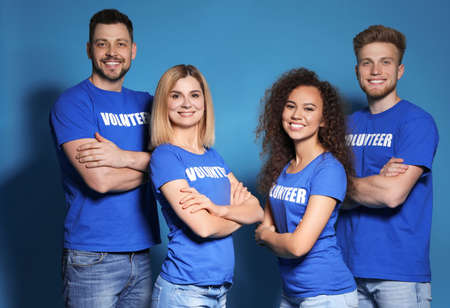 Team of volunteers in uniform on blue background