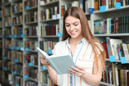 Young woman reading book near shelving unit in library