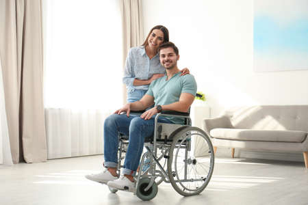 Young woman with man in wheelchair indoors Reklamní fotografie - 129176419