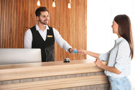 Client paying with credit card for service to receptionist at desk in lobby Stock fotó