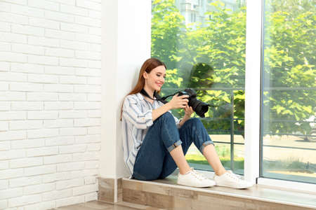 Professional photographer with modern camera sitting near window indoors