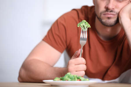 Unhappy man with broccoli on fork at table, closeup Reklamní fotografie