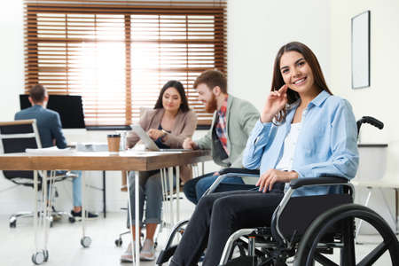 Young woman in wheelchair with colleagues at office Reklamní fotografie - 129176447