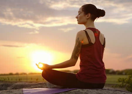 Young woman practicing zen yoga at sunrise outdoors