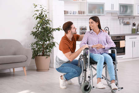 Young man with woman in wheelchair indoors Reklamní fotografie - 129176449