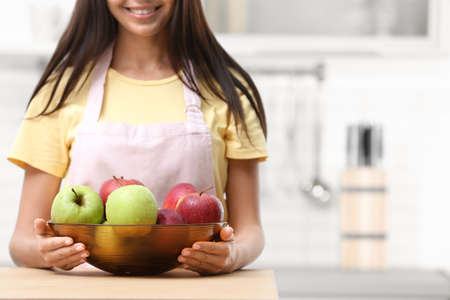 Woman with bowl of fresh apples at table in kitchen, closeup. Space for text