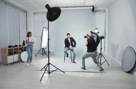 Professional photographer with assistant taking picture of young man in modern studio Stok Fotoğraf