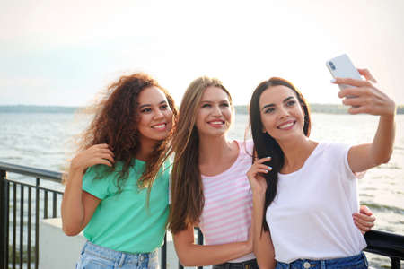 Happy young women taking selfie outdoors on sunny day Stockfoto