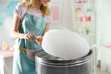 Woman making cotton candy using modern machine indoors, closeup