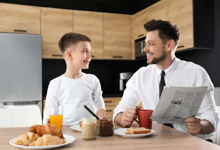 Dad and son having breakfast together in kitchen Stockfoto