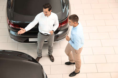 Young salesman working with client in modern car dealership, above view