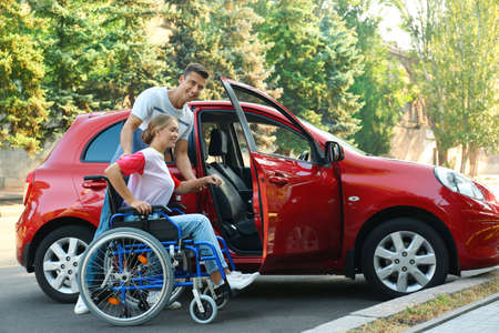 Young man helping disabled woman in wheelchair to get into car outdoors