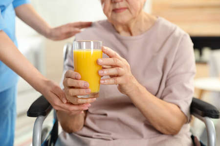Nurse giving glass of juice to elderly woman indoors, closeup. Assisting senior people