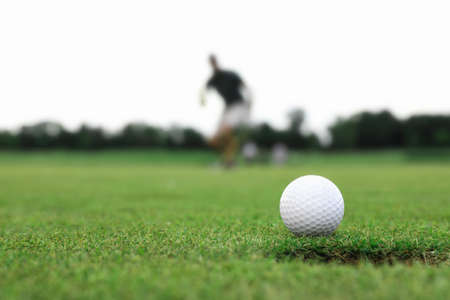 Man playing golf on green course, ball in focus. Sport and leisure Foto de archivo - 129246446