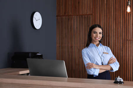 Portrait of receptionist with headset at desk in lobby