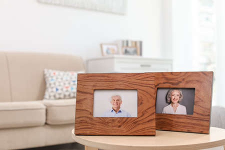 Portraits in wooden frames on table indoors Standard-Bild - 129175169