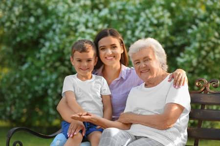 Grandmother with her family sitting on bench in park Standard-Bild - 129175176