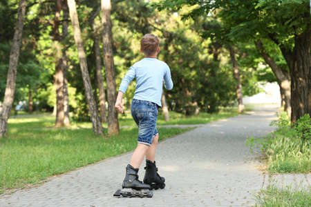 Little boy roller skating in park, back view