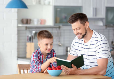 Dad and son reading interesting book in kitchen Stockfoto