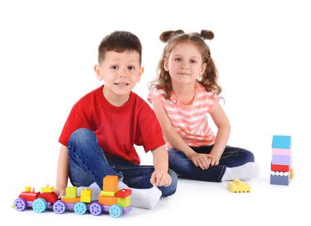 Lindos niños pequeños jugando con juguetes sobre fondo blanco.