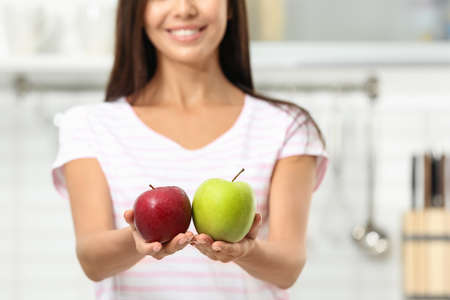Woman holding fresh apples in kitchen, closeup Stock Photo