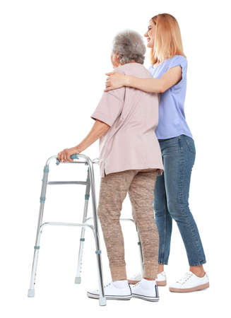 Caretaker helping elderly woman with walking frame on white background Standard-Bild - 129175206