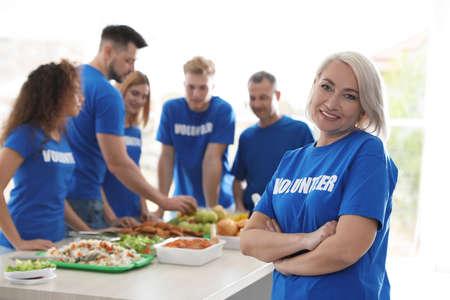 Team of volunteers near table with food indoors