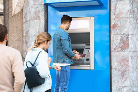 Young people standing in queue to cash machine outdoors Stockfoto