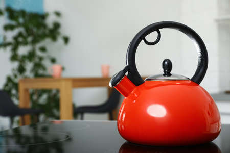 Modern kettle with whistle on stove in kitchen, space for text Stock fotó