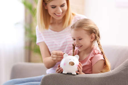 Family with piggy bank and money at home