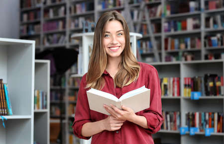 Young pretty woman with book in library