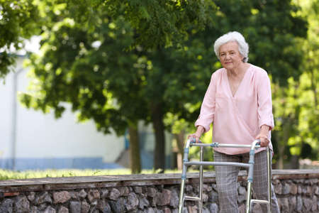 Elderly woman with walking frame outdoors. Medical help