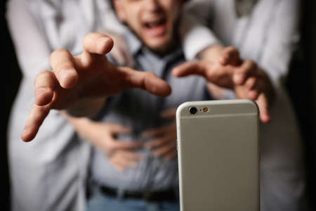 Emotional man reaching for smartphone while medical workers holding him back on black background, closeup. Addiction concept
