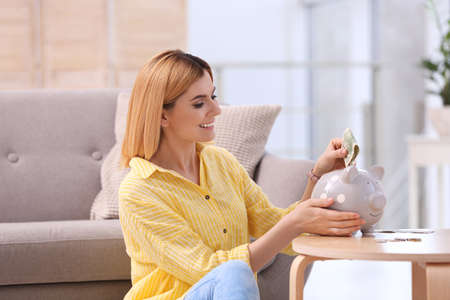 Woman with piggy bank and money at home