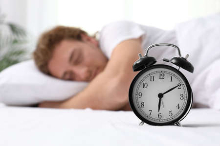 Alarm clock and blurred sleepy man on background, space for text. Bedtime 写真素材