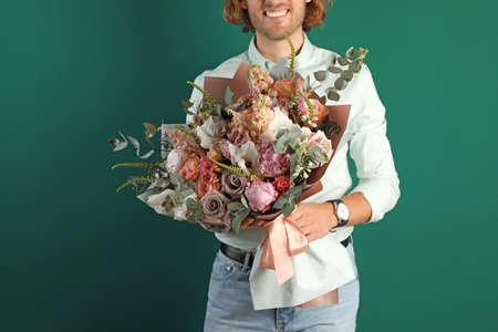 Man holding beautiful flower bouquet on green background, closeup view