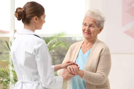 Nurse comforting elderly woman indoors. Assisting senior generation