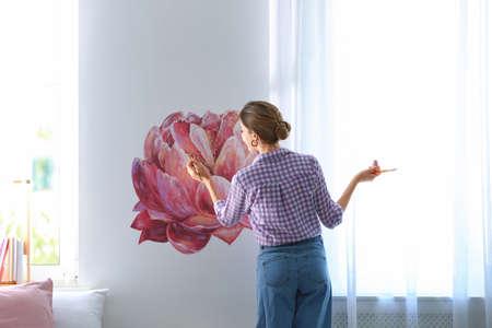 Jeune architecte d'intérieur peignant des fleurs sur le mur dans une chambre moderne